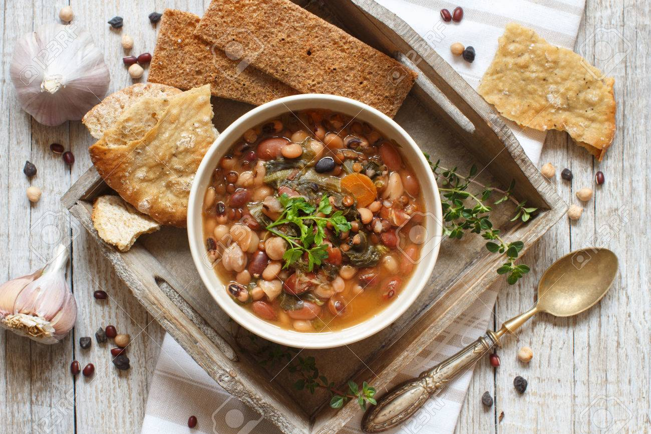 Cooked legumes and vegetables in a bowl on the old wooden table Archivio Fotografico - 56248685