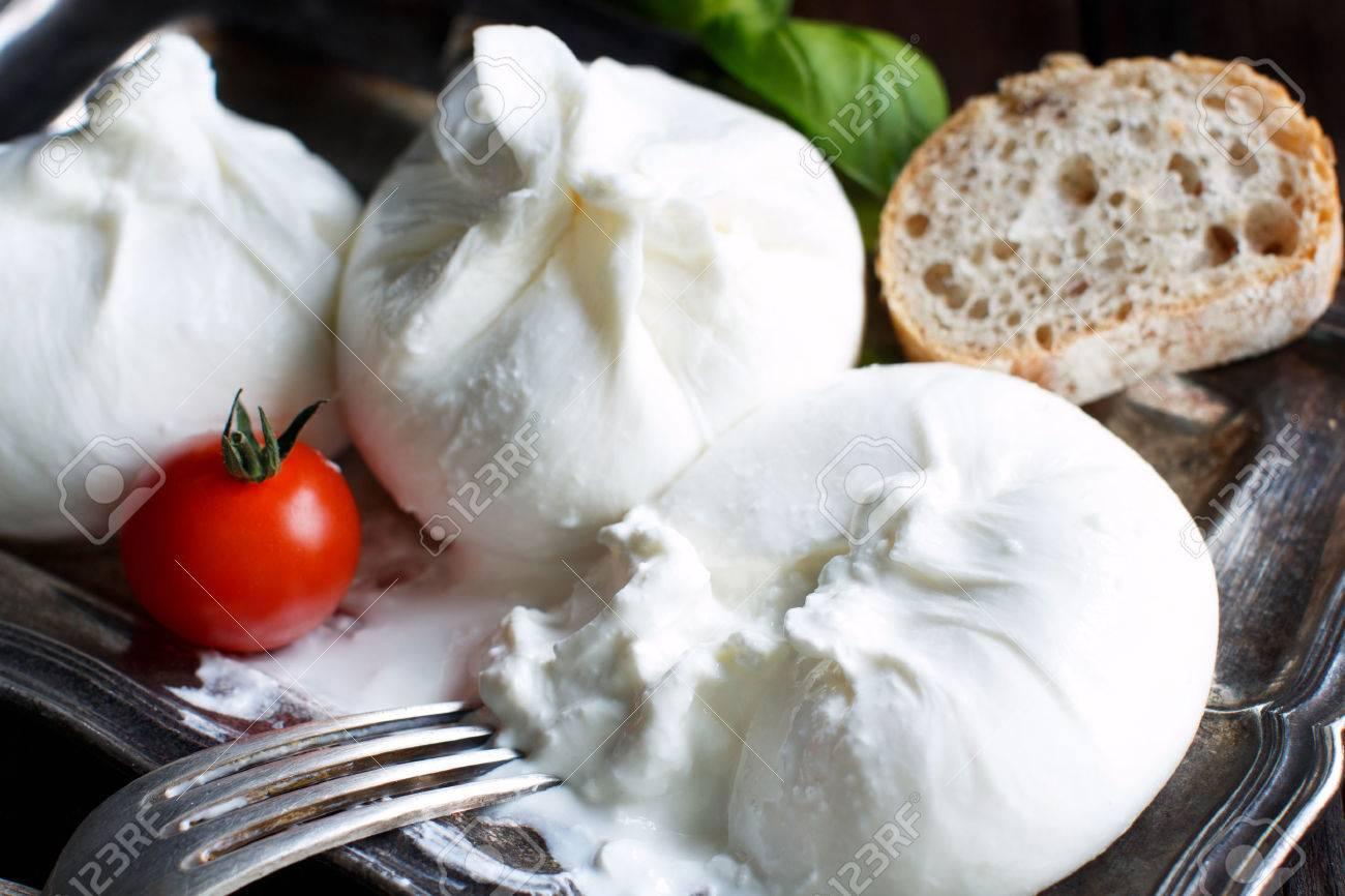 Italian cheese burrata, tomatoe and basil close up Archivio Fotografico - 71477988