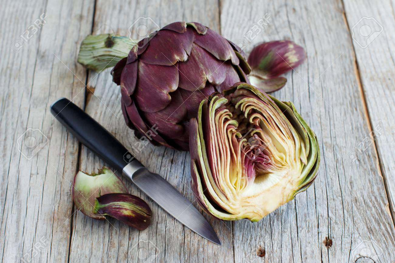 Roman Artichokes on a wooden board with knife Archivio Fotografico - 73418771