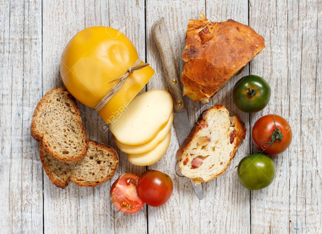 Scamorza cheese, tomatoes and bread on a wooden table Archivio Fotografico - 75336109