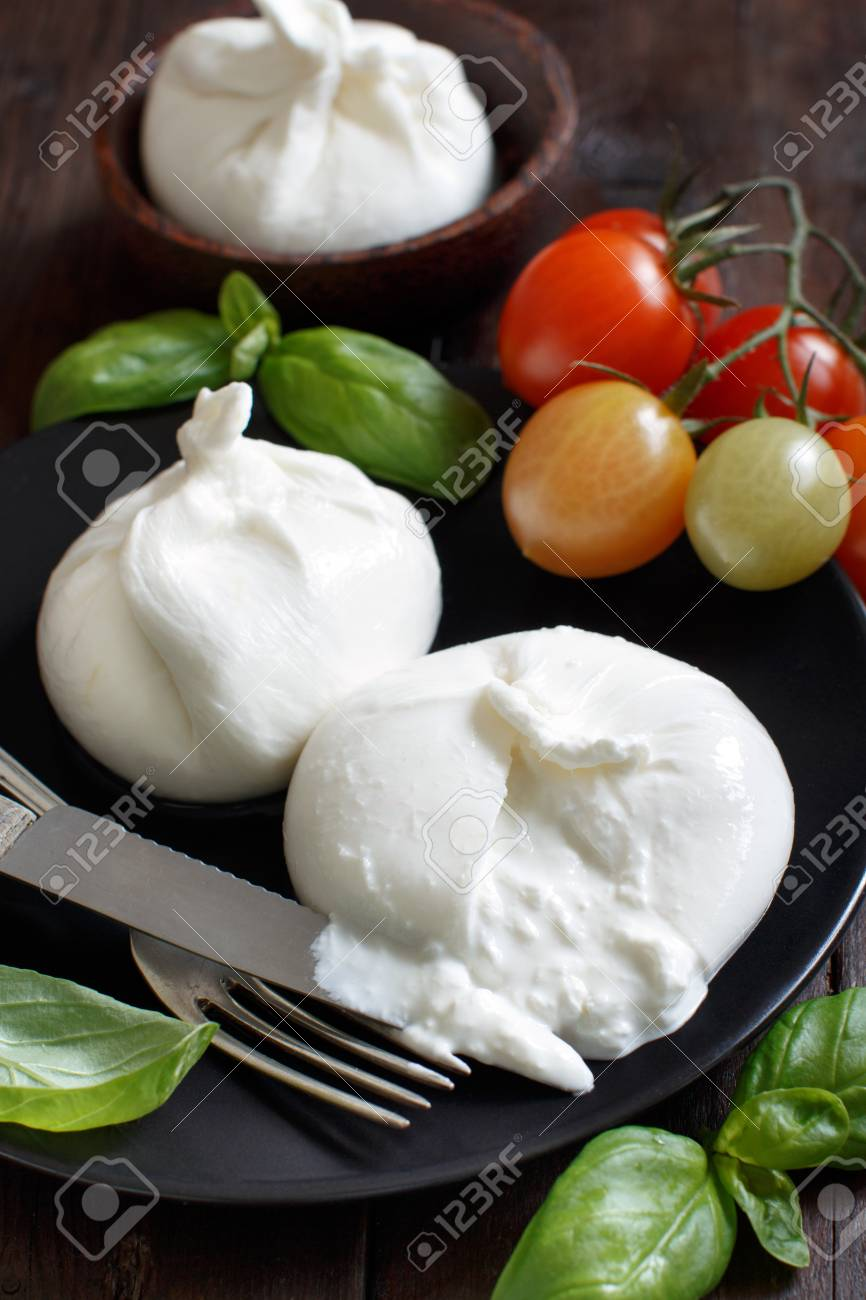 Italian cheese burrata with tomatoes and herbs on a dark background Archivio Fotografico - 75336132