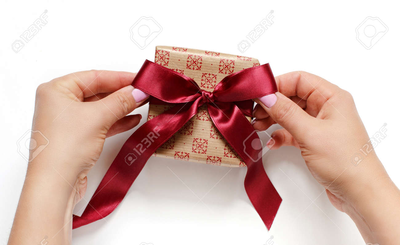 Hands tie a ribbon bow on anEcru gift box on white top view - 157446594