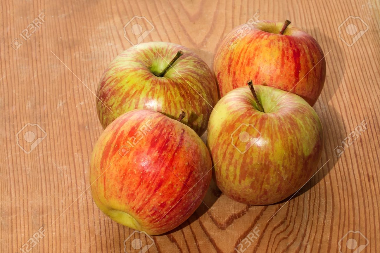 four apples on wooden table stock photo picture and royalty free