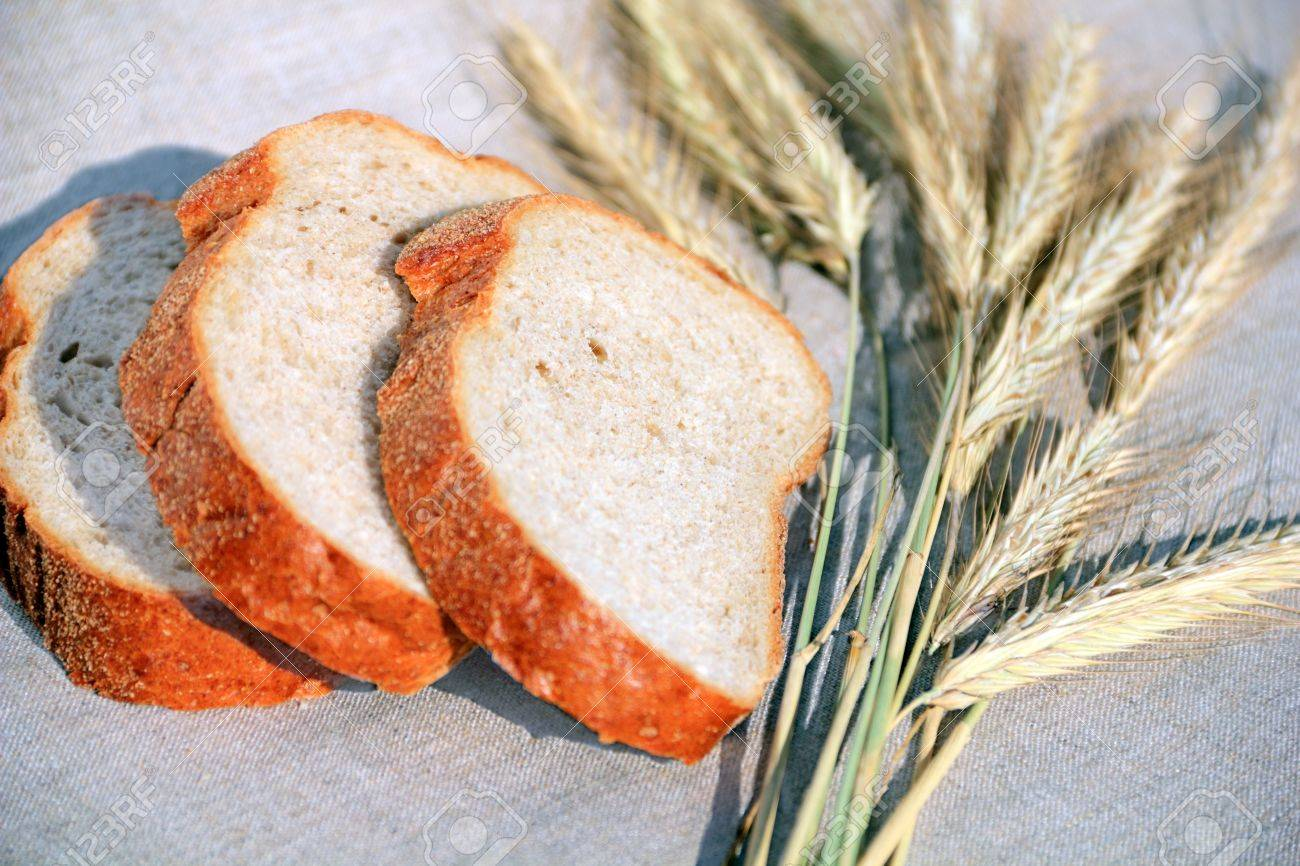 pieces of fresh soft bread with cereal ears on linen Stock Photo - 10032177
