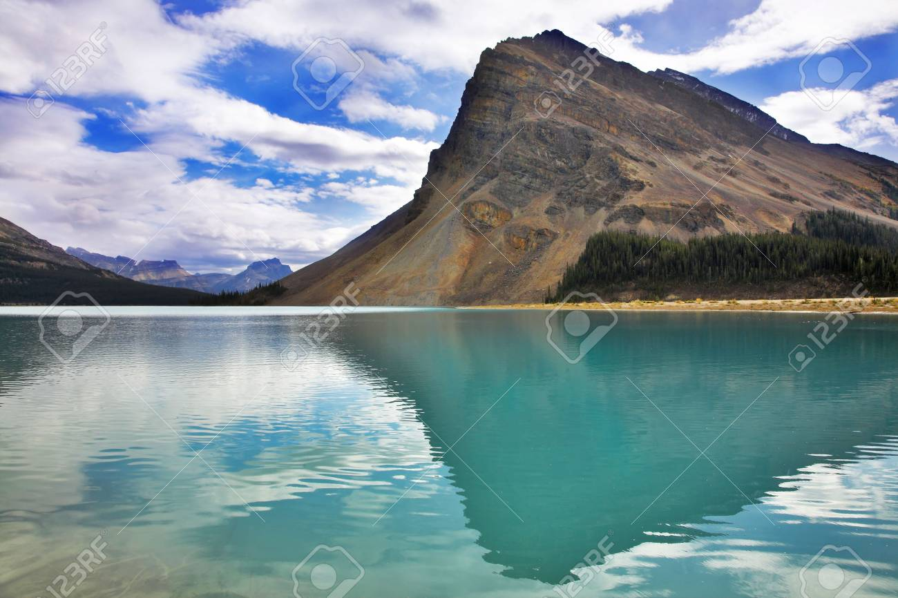 The huge rock of the triangular form is reflected in emerald waters of cold mountain lake Stock Photo - 5515230