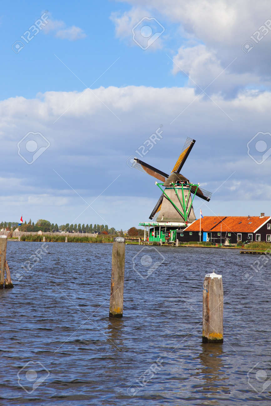 Traditional windmills and berthing bumpers on coast of the channel in Holland. Stock Photo - 8331472