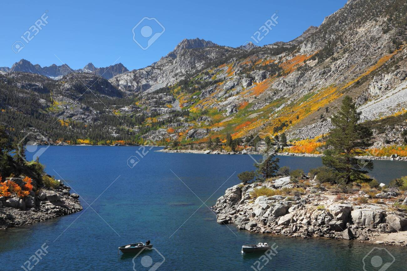 Picturesque island on mountain lake. Fishing boats are moored about island Stock Photo - 8387660
