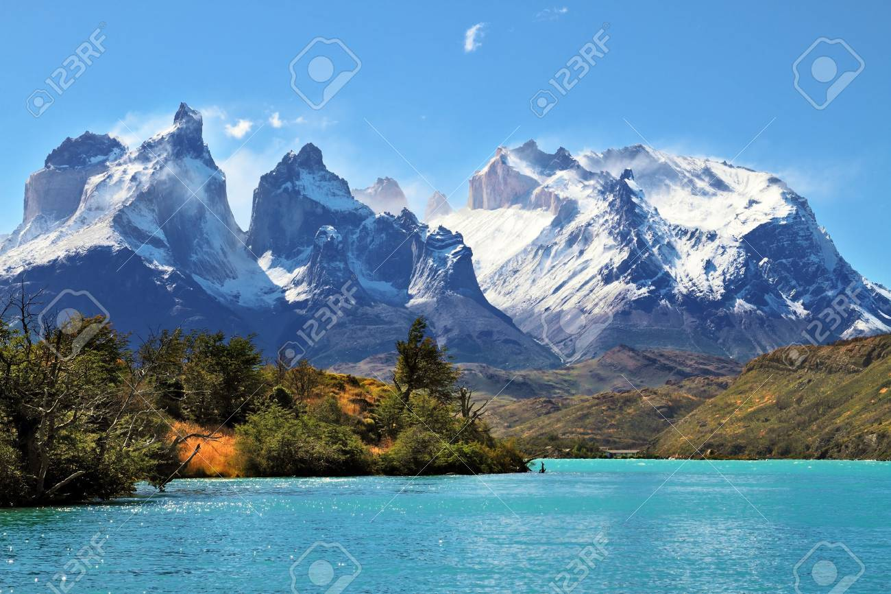 Azure Lake Pehoe at the foot of the magnificent snow-covered cliffs of Los Kuernos. National Park Torres del Paine, Chile - 26138237