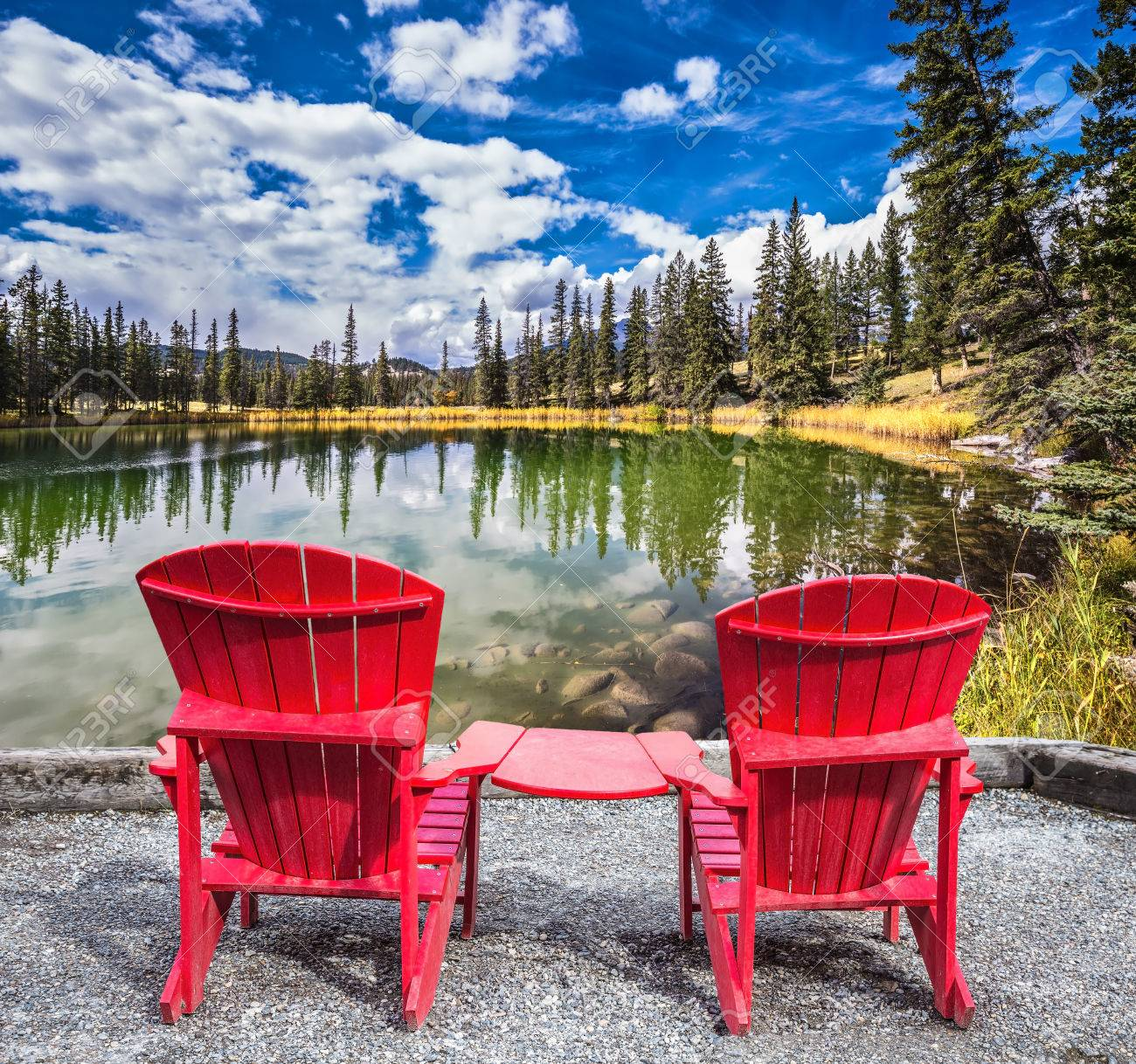 two red plastic chairs on the lake on shores of the lake grow