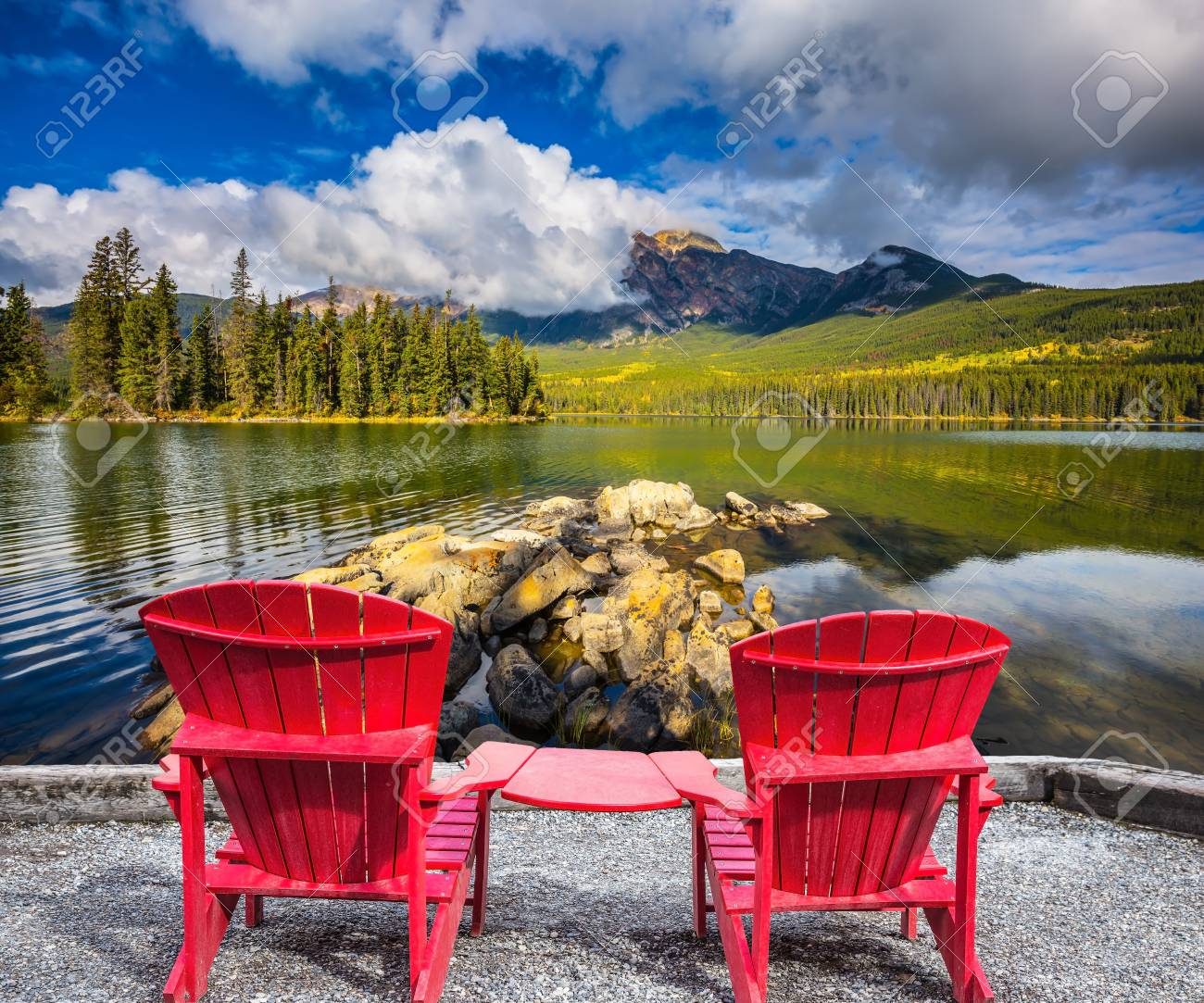 Pyramid Mountain reflected in Pyramid Lake  Two red chaise lounges