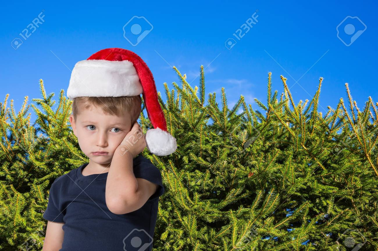 Adorable boy with blue eyes in a red cap of Santa Claus is sad