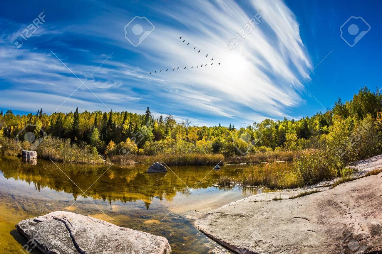 Huge flat stones in riverbed of Winnipeg River  Indian summer