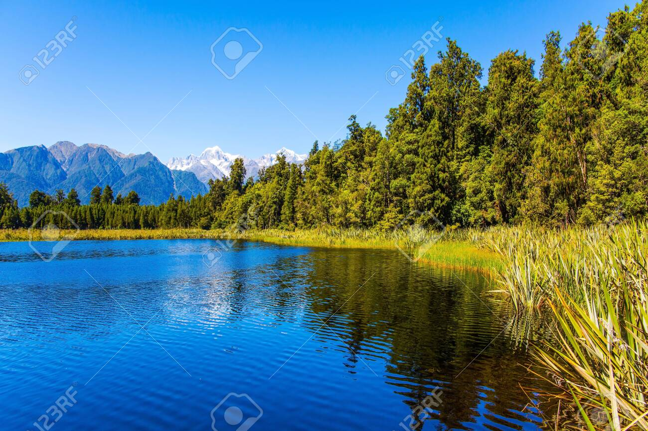 The famous lake Matheson reflects Mount Cook and Mount Tasman. Lake Matheson is picturesque glacial lake in the South Island of New Zealand. The concept of ecological, active and photo tourism - 133246511