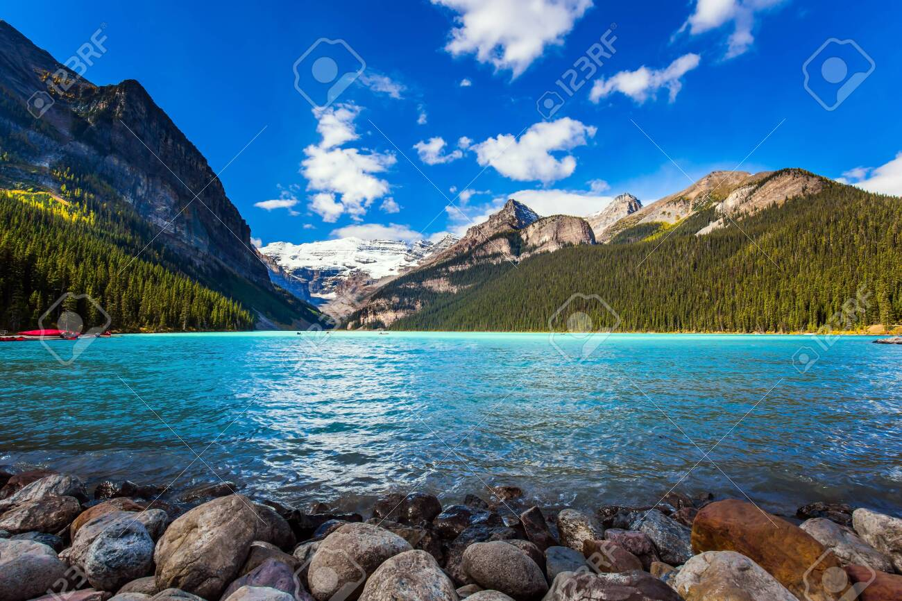 Glacial Lake Louise - the lake with azure water is surrounded by forests and mountains. Red canoes for tourists are moored to the coast. Rocky Mountains. The concept of active and photo tourism - 142288659