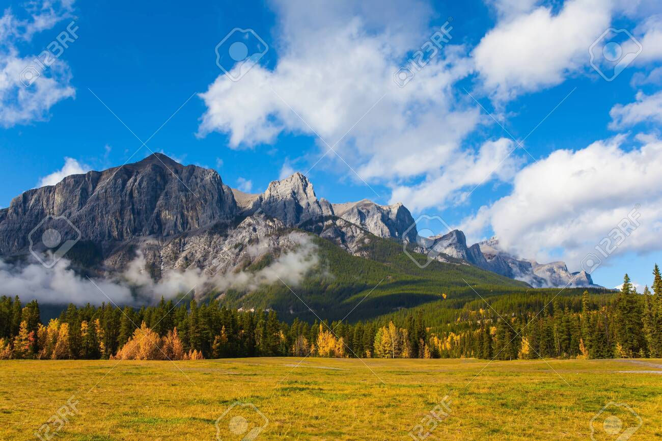 Lush bright autumn day in the Canadian Rockies. The majestic Rocky Mountains. The Three Sisters Mountain is covered in lush white clouds. The concept of active, ecological and photo tourism - 147892696