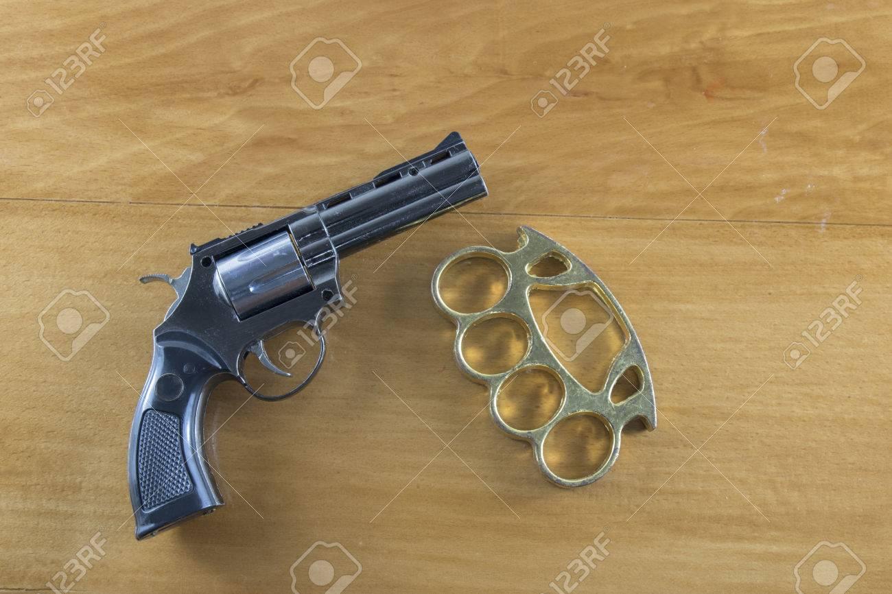 Gun Brass Knuckles On The Wooden Floor