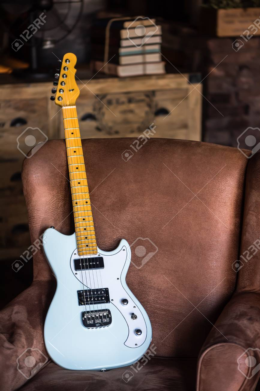 Electric Guitar Leaning Against A Couch With Grunge Background