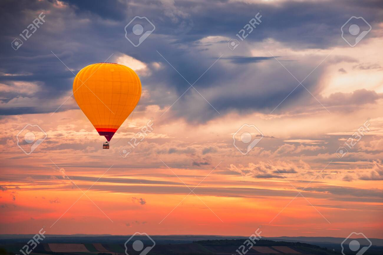 Hot Air Baloon Flying with Beautiful Colorful Dramatic Sky at Sunset - 135044593