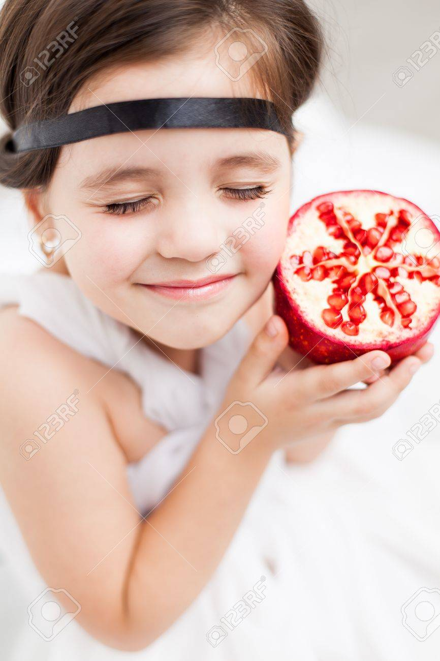 Portrait of a cute little girl model looks in luxurious white dress with makeup and hair decoration. Posing against a white wall with a pomegranate in her hand. Stock Photo - 16253302
