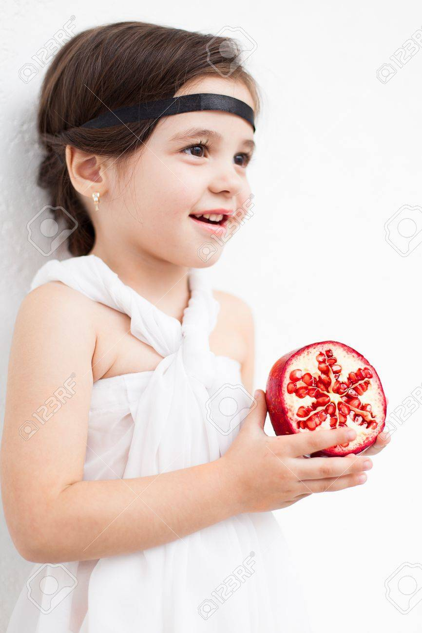 Portrait of a cute little girl model looks in luxurious white dress with makeup and hair decoration. Posing against a white wall with a pomegranate in her hand. Stock Photo - 16253271