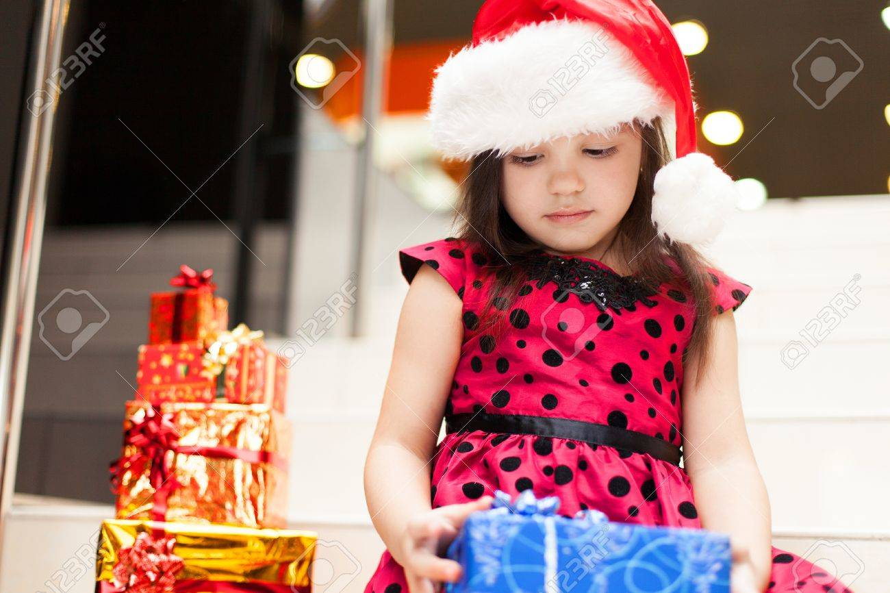 Cute little girl posing with gifts in the Christmas hat and a luxurious dress, sitting on the stairs in a big shopping mall. Stock Photo - 16253193