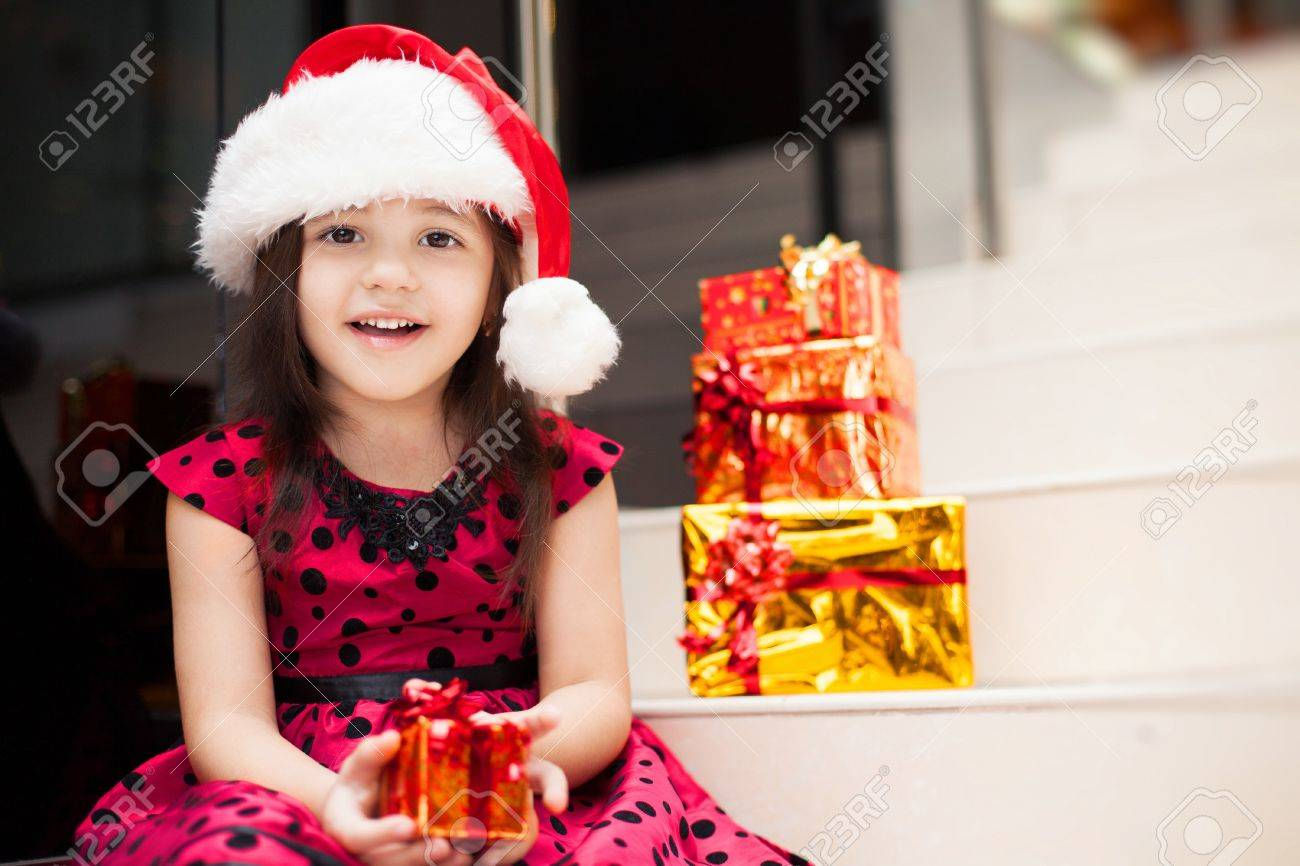 33d0a37d014c0 Cute little girl posing with gifts in the Christmas hat and a luxurious  dress, sitting