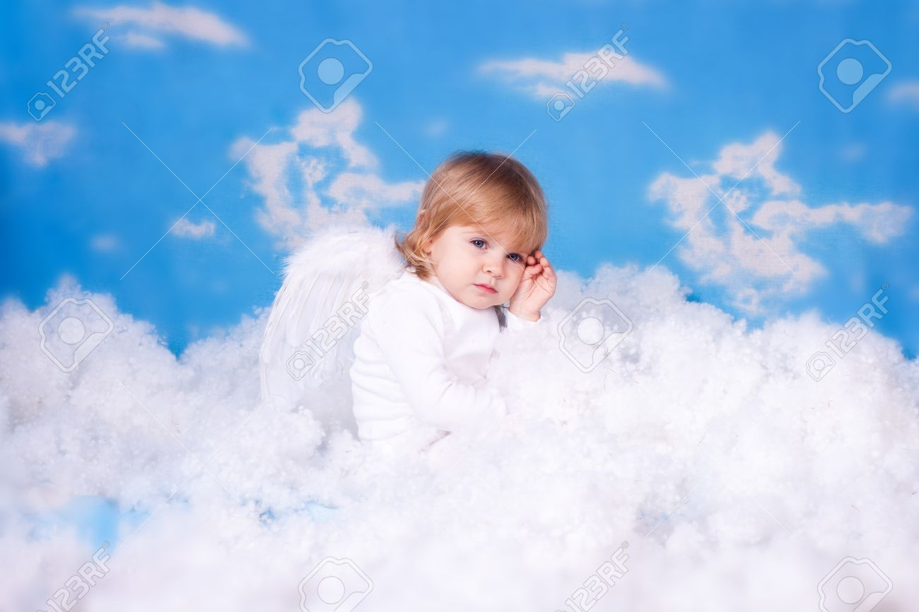 Beautiful Baby Girl With Angel Wings In White Clothes Posing On A Background Of The Sky