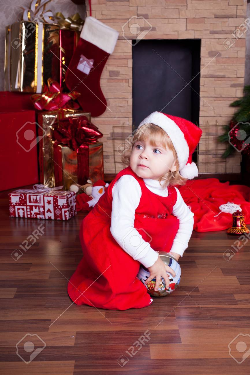 Beautiful blond little girl in a red Christmas hat posing by the fireplace on Christmas Eve, enjoys gifts  A series of photos in my portfolio Stock Photo - 16292545