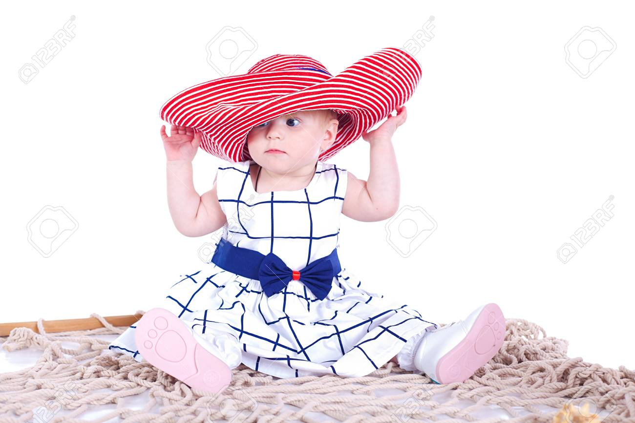 small beautiful child playing with a big red hat in the studio on a white background Stock Photo - 16302468