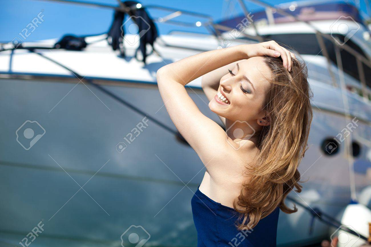 Young beautiful brunette woman relaxing on the dock near the boat on a sunny day in spring - 16349381
