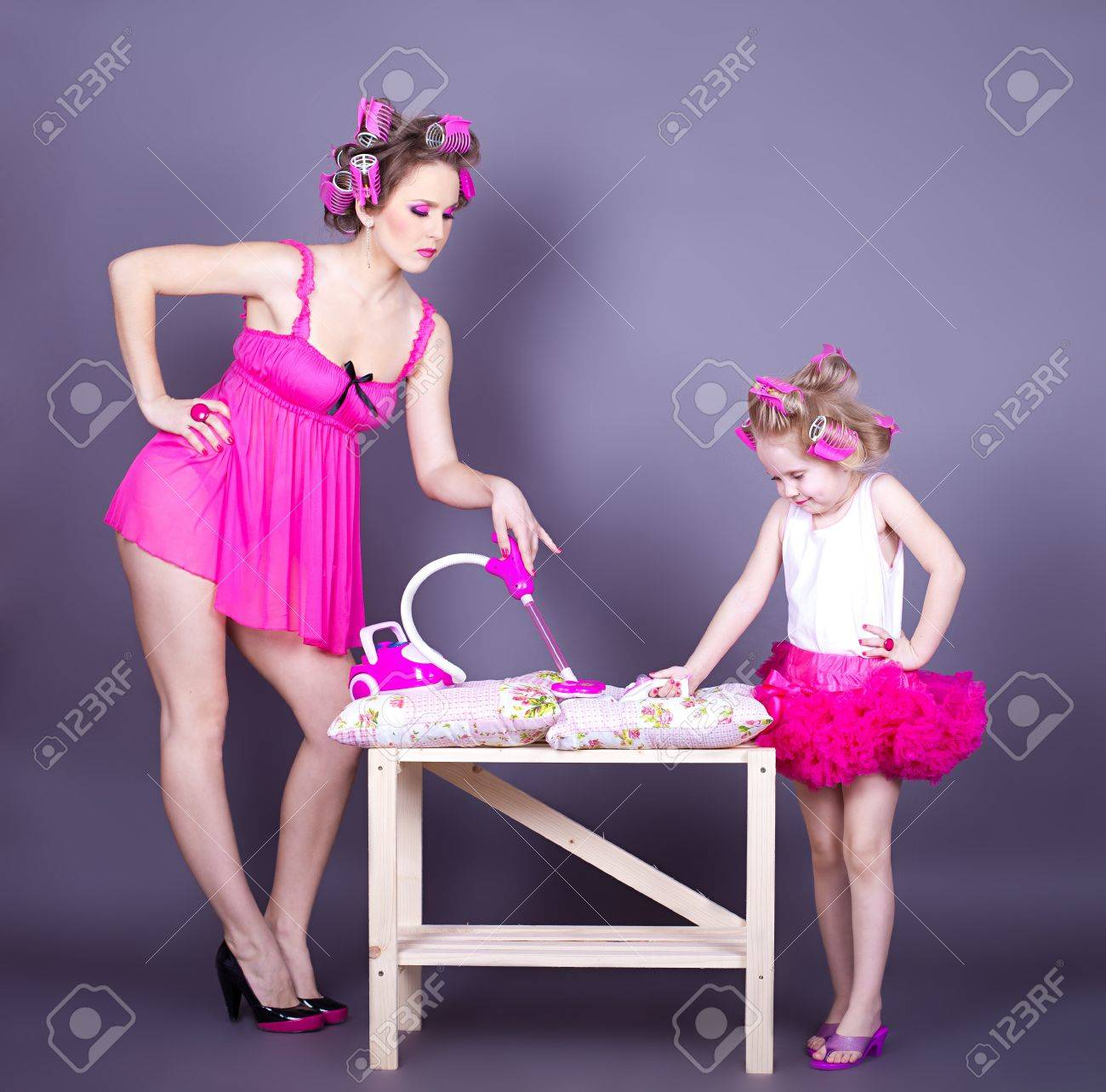 A beautiful young mother with her daughter in the form of cheerful housewives Studio shot on a gray background Series - 16491140