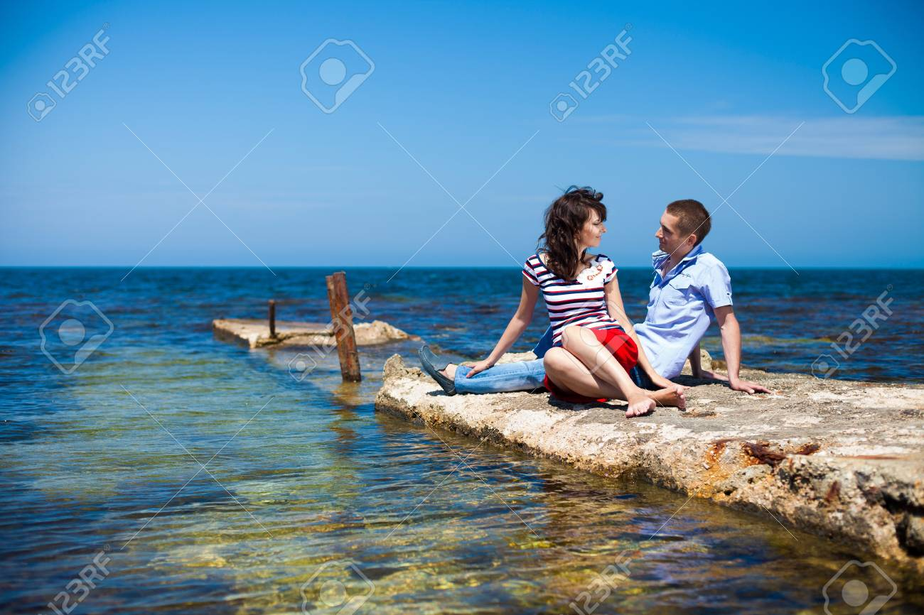 Couple in love, young guy and a beautiful brunette girl posing in the beach, enjoying their summer holiday together Stock Photo - 16549018