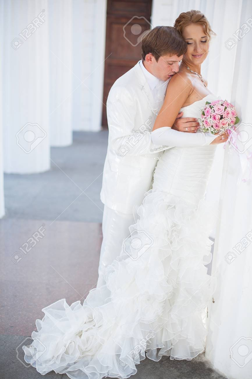 Young couple in love bride and groom posing near the white columns in their wedding day in the summer Stock Photo - 16536972