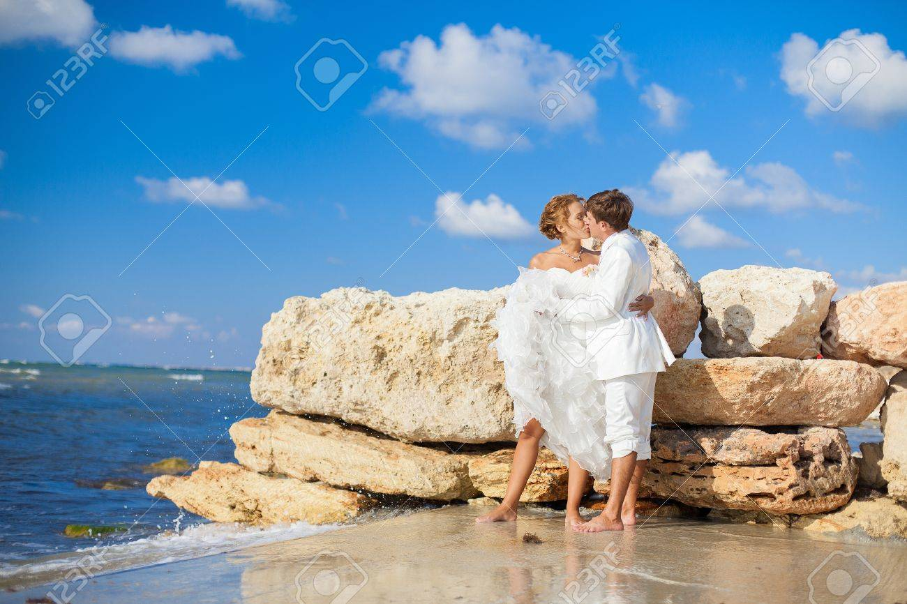 Couple in love young bride and groom hugging on the shore of the blue sea in a luxurious white dress posing next to a wall of yellow stones from the sea floor Wedding day in the summer Series - 16622673