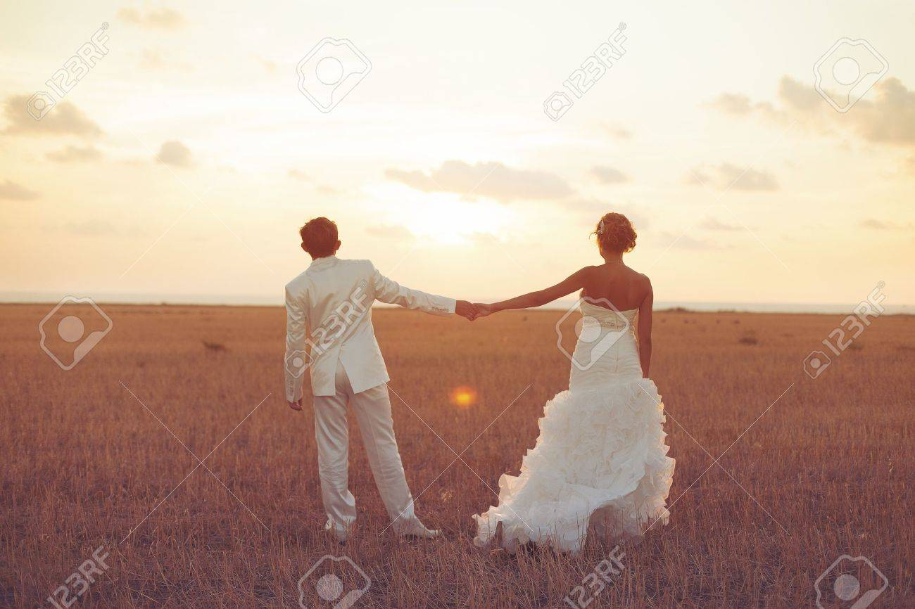 Young couple in love bride and groom posing in a field with yellow grass on sunset background in their wedding day in the summer Series - 16536974