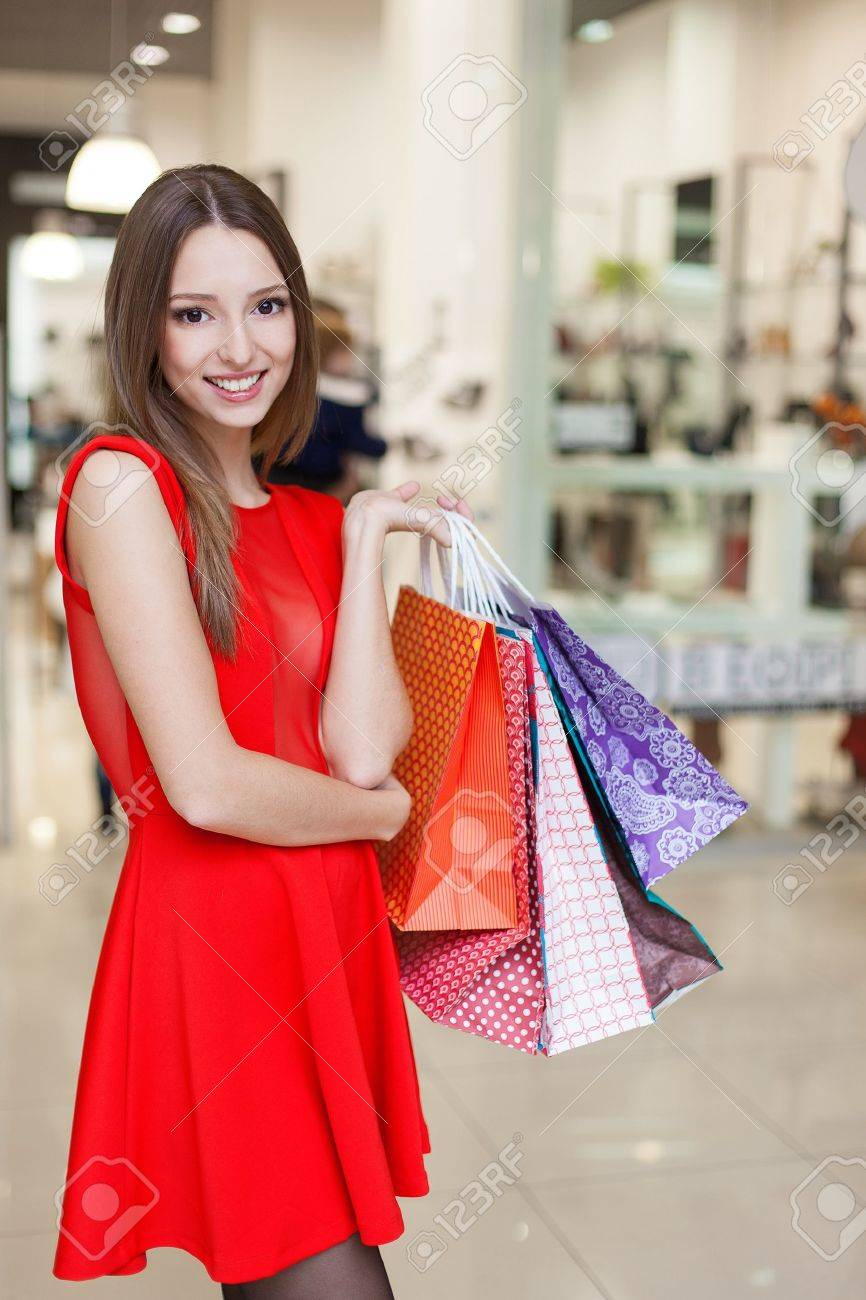 Beautiful young woman in a luxurious red dress posing with shopping bags in mall on the background of shop windows. Series. - 16637331