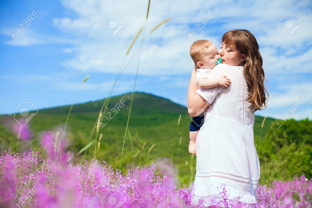 Beautiful young mother posing with a small child in her arms while standing in a field of purple flowers on the background of mountain and blue sky  Series Stock Photo - 16715529