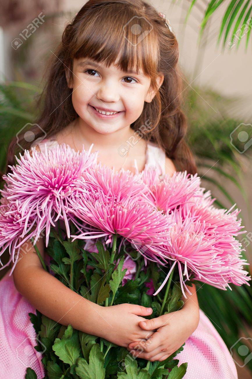 Beautiful little girl posing with a large bouquet of flowers in a luxurious pink dress at home Stock Photo - 16710938