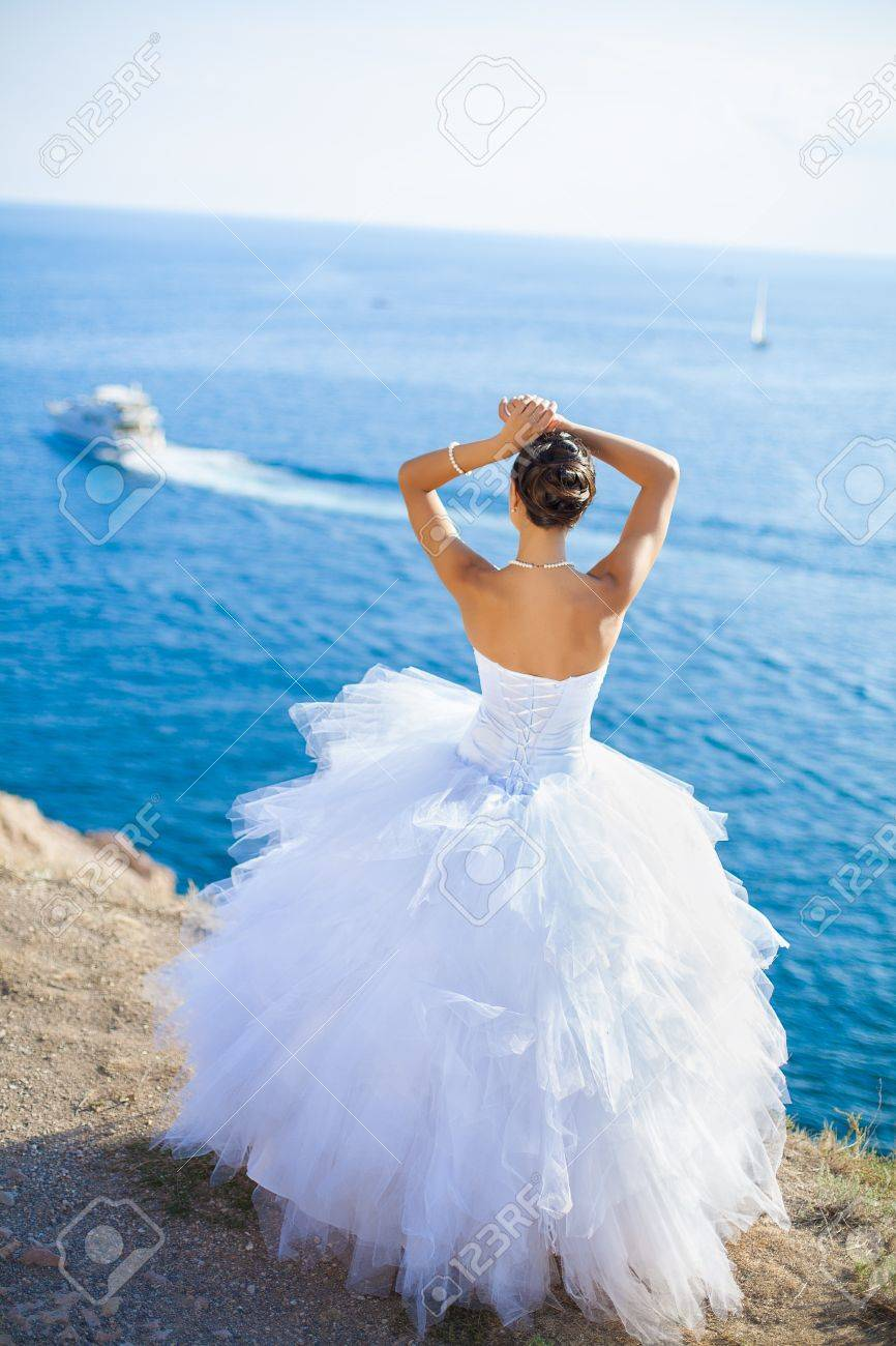 Happy Bride In White Dress Stands On Cliff On Background Blue ...