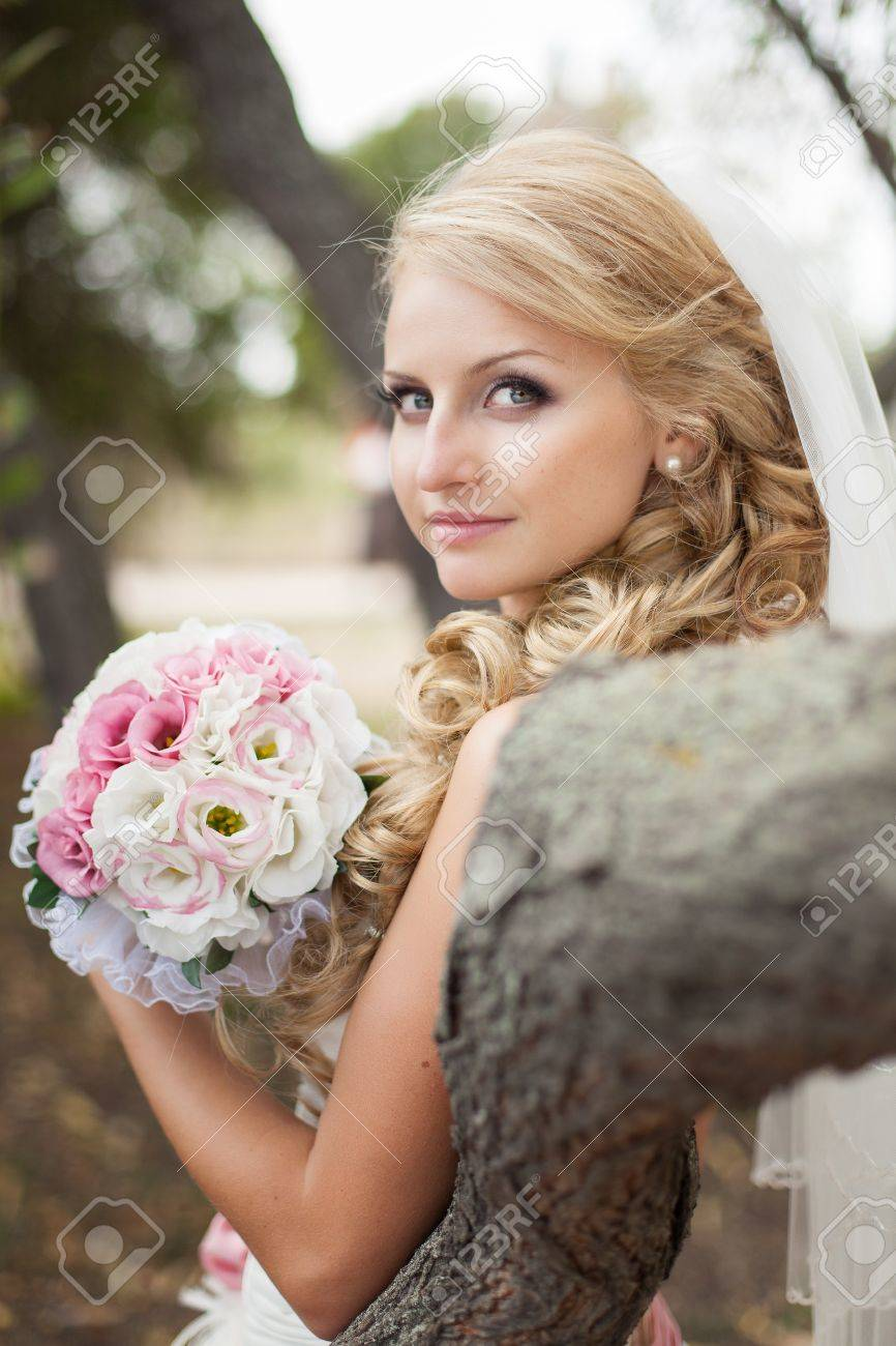 Attractive bride posing in the green leaves of the tree in her wedding day - 17152779