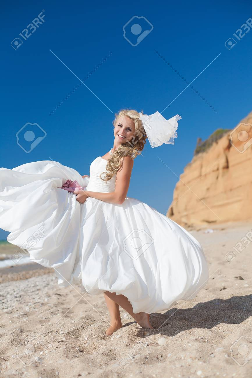 Attractive bride posing on the beach smiling and running on sand Stock Photo - 17152770