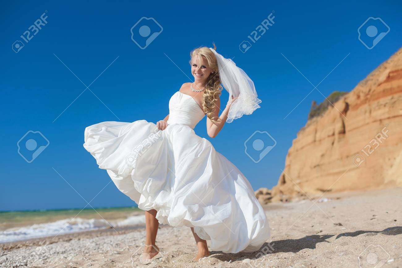 Attractive bride posing on the beach smiling and running on sand Stock Photo - 17152803