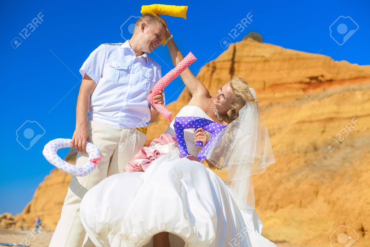 Wedding  couple posing on the shore and jokingly fight letters of the word  LOVE Stock Photo - 17152790