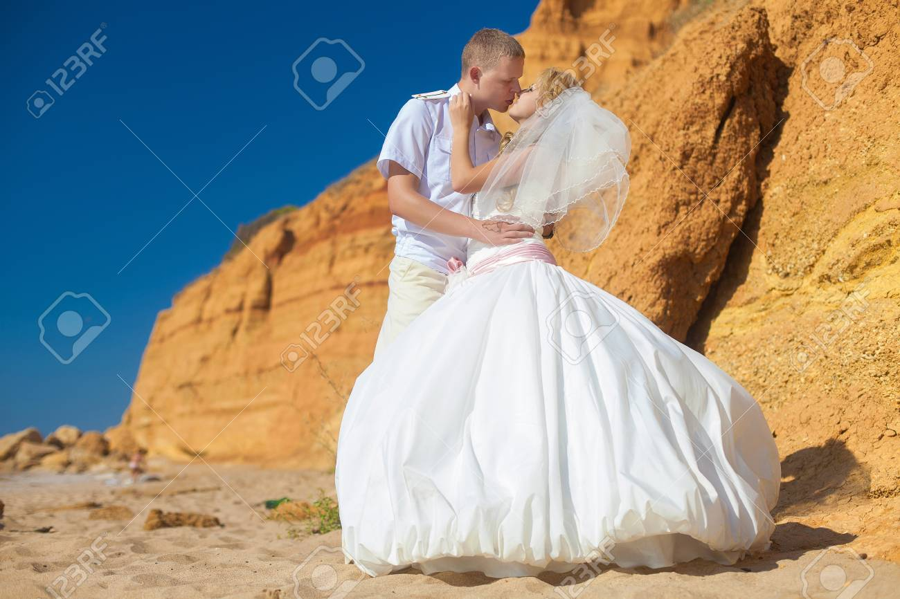 Couple in love bride and groom pose for embracing on background the rocks standing on sand by the sea, enjoying the moments of happiness in their wedding day Stock Photo - 17152774