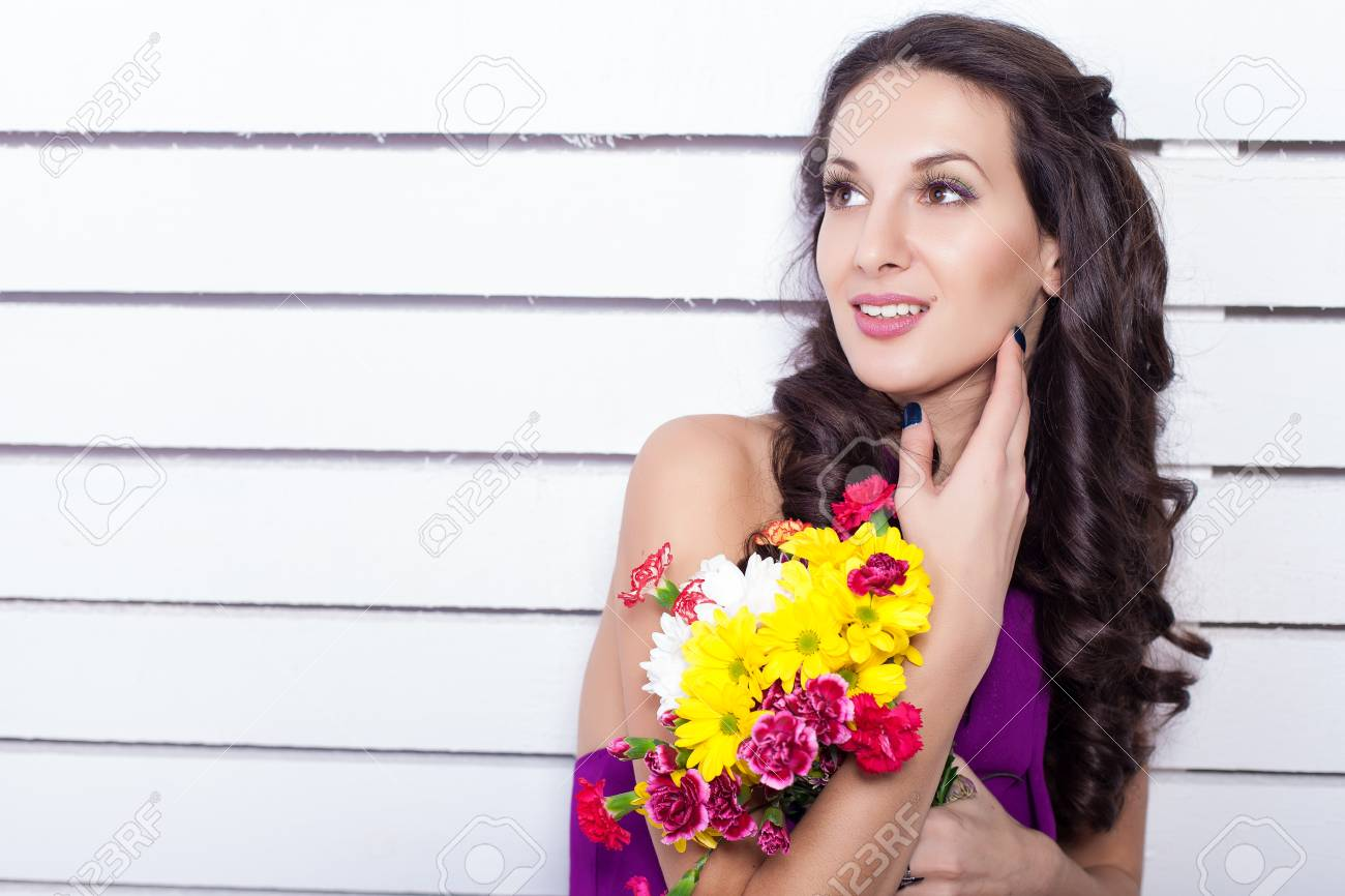 Elegant fashionable woman with flowers over wall background Stock Photo - 17342056