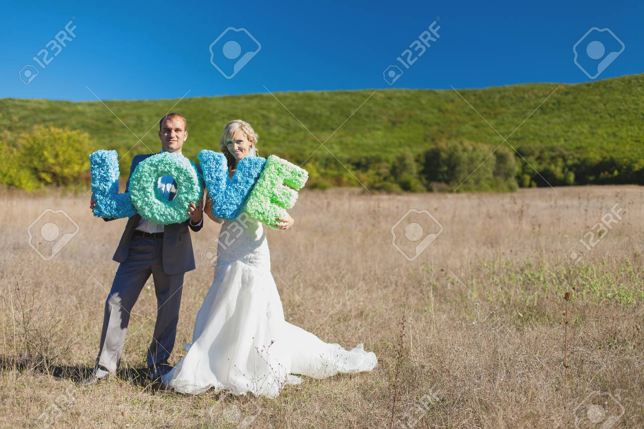 wedding  bride and groom holding letters of word LOVE Stock Photo - 17460826