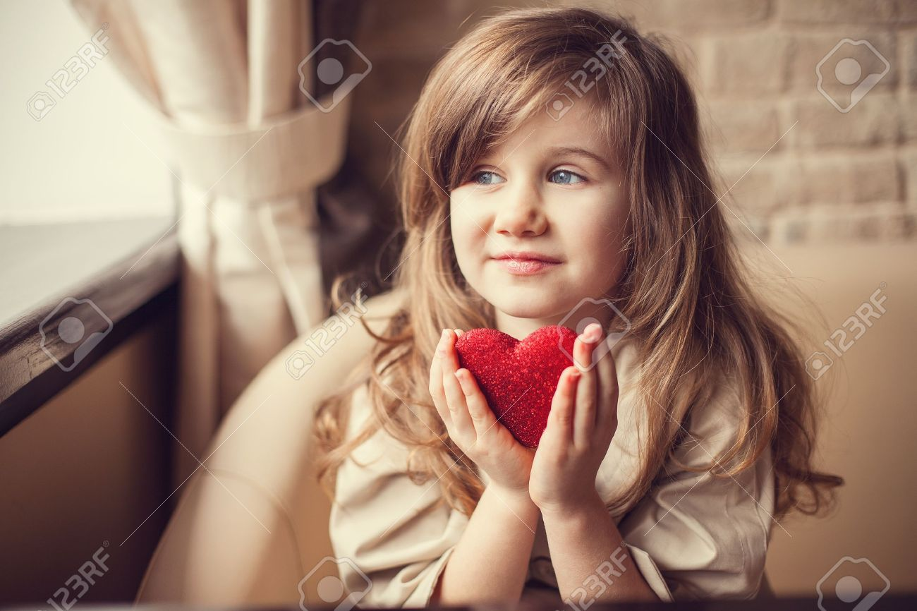 Valentine Day - dreaming cute child with red Heart in hands. - 17809989