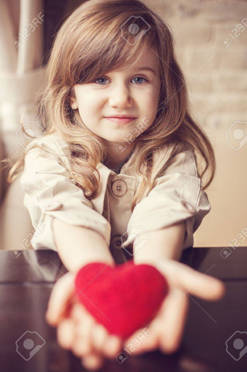 valentine day dreaming cute child with red heart in hands stock