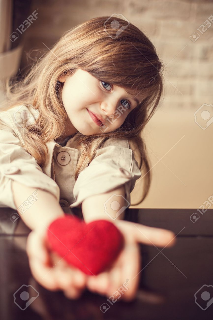 valentine day - dreaming cute child with red heart in hands. stock