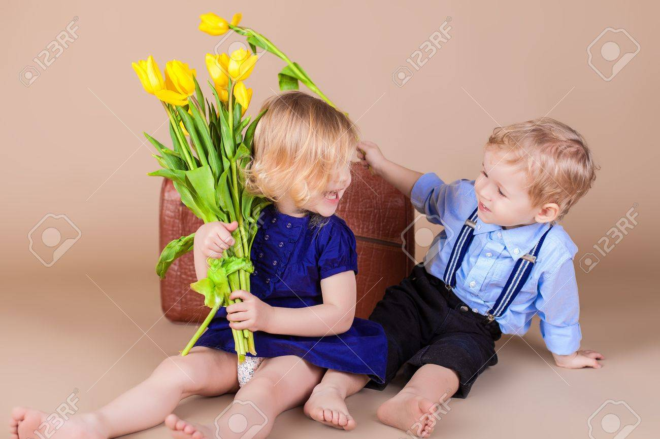 funny kids happy little boy giving a cute bouquet of yellow
